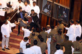 Parliament member Johnston Fernando who is backing newly appointed Prime Minister Mahinda Rajapaksa throws a chair at police who are there to protect parliament speaker Karu Jayasuriya (not pictured) during a parliament session in Colombo, Sri Lanka,