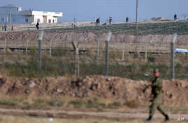 FILE - A Turkish soldier walks by the border fence with Syria while in the background, Kurdish fighters, top right, advance, as civilians, top left, flee the outskirts of Tal Abyad, Syria.