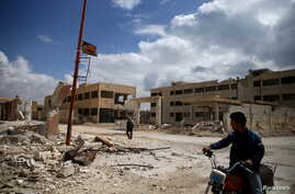 A man rides on a motorbike as another one walks past damaged buildings in the rebel-controlled area of al-Nashabyia town in Eastern Ghouta, Syria, April 13, 2016.