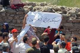 In this undated photo published by the U.S.-based Center for Human Rights in Iran, Iranian Azerbaijanis stage an annual July protest against discrimination targeting their community at Babak Fort in East Azerbaijan province. The slogan on the white b