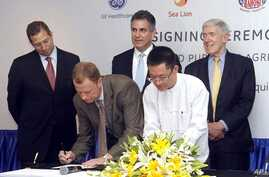 President and CEO of General Electric ASEAN, Stuart Dean, second from left, signs documents during the signing ceremony between Sea Lion Co. Ltd., General Electric Healthcare and Bahosi and Pun Hlaing Hospitals in Rangoon, Burma, July. 14, 2012.