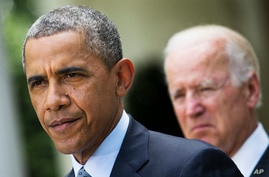 President Barack Obama, accompanied by Vice President Joe Biden, pauses while making a statement about immigration reform in the Rose Garden of the White House in Washington, June 30, 2014.