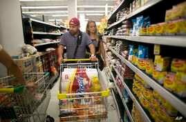 Venezuelan husband and wife Ramiro Ramirez and Tebie Gonzalez shop for food in Cucuta, Colombia, July 17, 2016, during the temporary opening of the long-closed border with Venezuela. The country's economic crisis has brought shortages; U.S. firms and