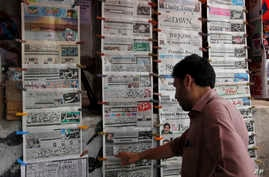 A man reads the morning newspaper displaying the front-page story of the disqualification of Prime Minister Nawaz Sharif by Supreme Court at a stall in Islamabad, July 29, 2017.