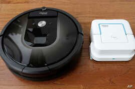 FILE - In this Aug. 25, 2016, photo, an iRobot Roomba vacuum, left, and Braava Jet floor cleaner are displayed at the company's headquarters in Bedford, Mass.