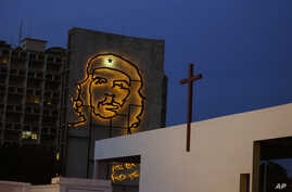 "A sculpture of revolutionary hero Ernesto ""Che"" Guevara is lit up on a government building in Revolution Square beside an altar under construction ahead of Pope Francis' Mass in Havana, Cuba, Sept. 10, 2015."
