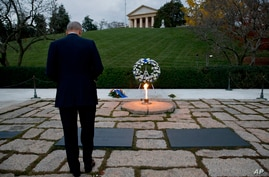 Attorney General Eric Holder pays his respects at the grave of John F. Kennedy at Arlington National Cemetery, Nov. 22, 2013, on the 50th anniversary of Kennedy's death.