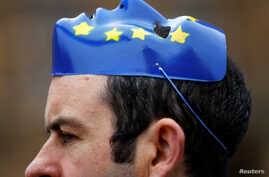 An anti-Brexit protester wears a EU face mask on his head outside the Houses of Parliament in London, Nov.14, 2017.
