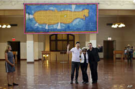 Bono, right, and The Edge, left, of the Irish rock band U2, flank Yoko Ono, the widow of John Lennon, at the unveiling of a giant tapestry depicting the island of Manhattan as a yellow submarine piloted by a waving Lennon at Ellis Island,  July 29, 2