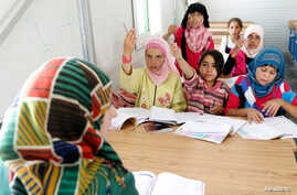Syrian refugee children attend a class during the opening of a new school at the Al Zaatri refugee camp in the Jordanian city of Mafraq, near the border with Syria June 4, 2013.