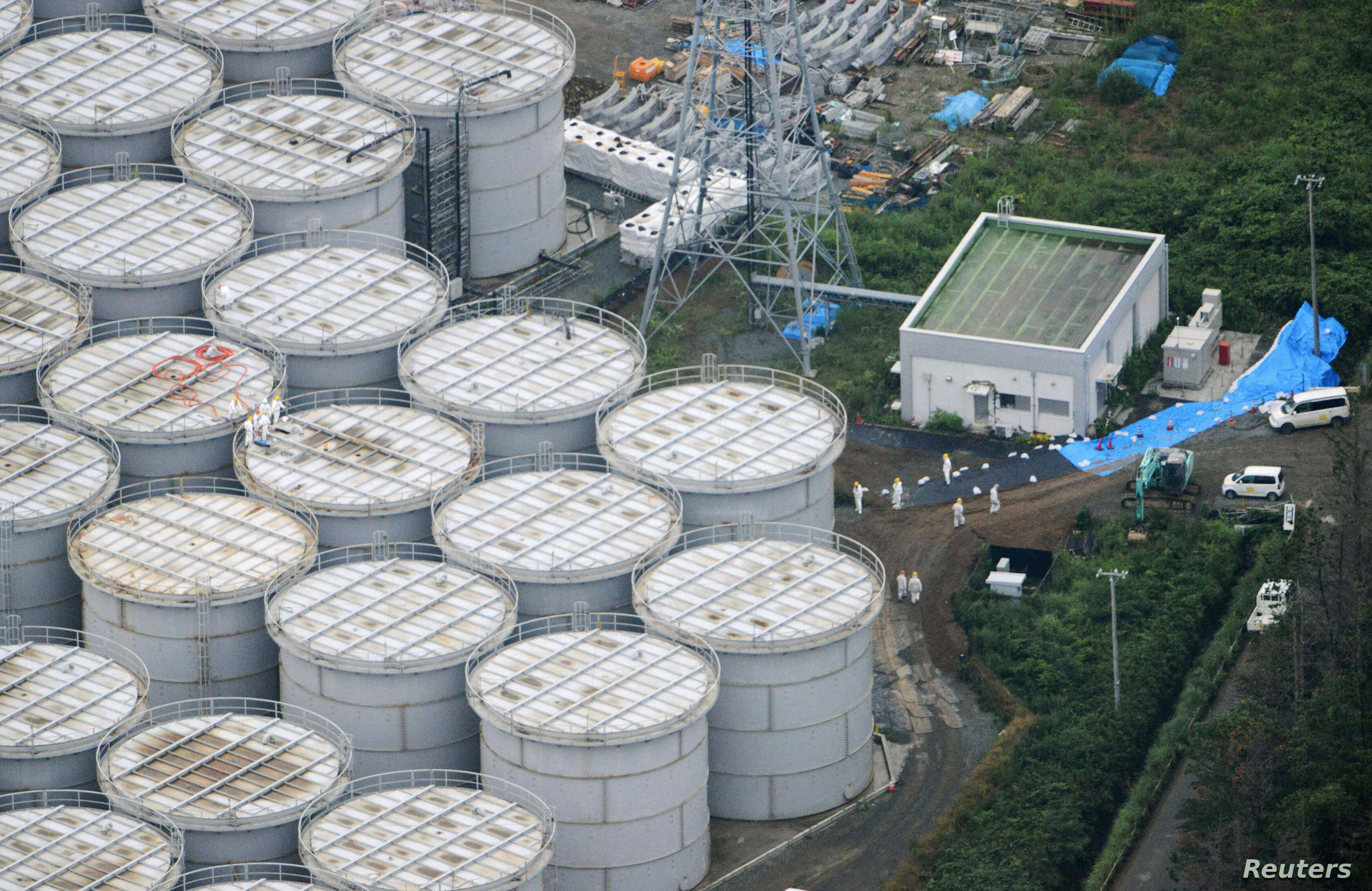 An aerial view shows workers wearing protective suits and masks working atop contaminated water storage tanks at Tokyo Electric Power Co. (TEPCO)'s tsunami-crippled Fukushima Daiichi nuclear power plant in Fukushima, in this photo taken by Kyodo Augu