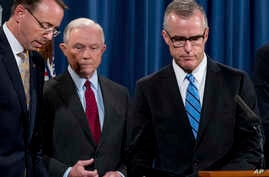 FBI Acting Director Andrew McCabe, right, accompanied by Attorney General Jeff Sessions, second from left, Deputy Attorney General Rod Rosenstein, takes the podium at a news conference at the Department of Justice, July 20, 2017, in Washington.