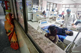A woman looks into the intensive care unit (ICU) at the Baba Raghav Das hospital in the Gorakhpur district, India, Aug. 14, 2017.