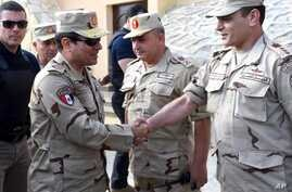 In this picture provided by the office of the Egyptian Presidency, Egyptian President Abdel-Fattah el-Sisi, second left, greets members of the Egyptian armed forces in Northern Sinai, Egypt, July 4, 2015.