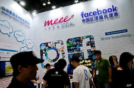 FILE - Visitors are seen at a social network company booth at the 2016 Global Mobile Internet Conference (GMIC) in Beijing, China, April 28, 2016. Last year, China passed a cybersecurity law that foreign companies say might isolate Chinese industries