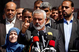 Hamas Chief Ismail Haniyeh gestures during a news conference as the wife of slain senior Hamas militant Mazen Fuqaha stands next to him, in Gaza City, May 11, 2017.