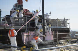 Workers are trying to remove unused nuclear fuel assemblies stored in the spent fuel pool tsunami-crippled Fukushima Daiichi Nuclear Power Plant No. 4 reactor building, July 19, 2012.