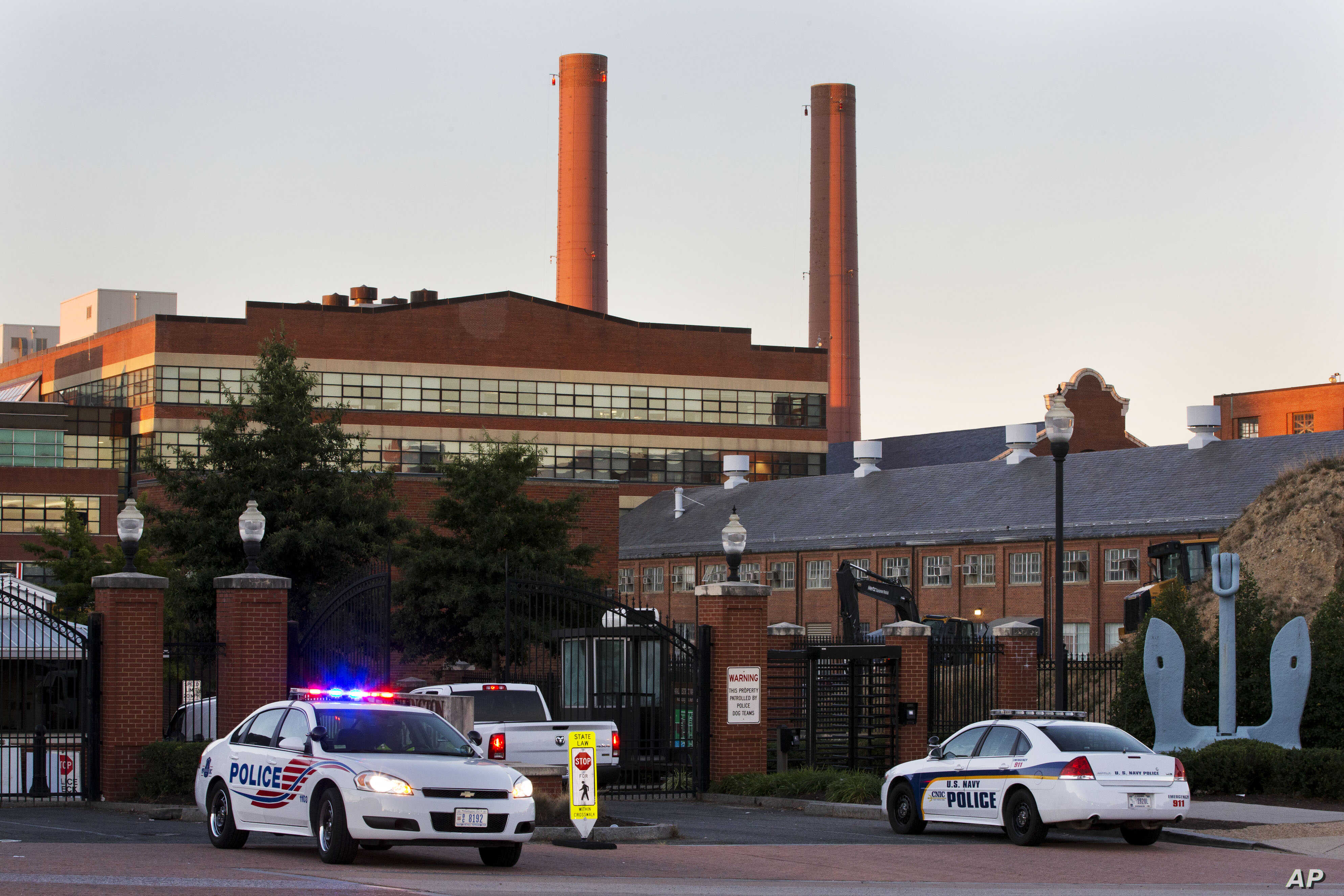 Police cars line the gate in the early morning as essential personnel only are allowed into a closed Washington Navy Yard in Washington, Sept. 17, 2013.