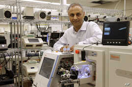 In this Aug. 10, 2015, photo, Dr. Akhilesh Pandey, a researcher at Johns Hopkins University, poses alongside a mass spectrometer in his laboratory in Baltimore. Pandey's research analyzes both adult and fetal tissue, and by identifying which proteins