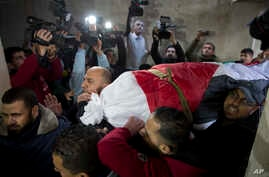 Mourners carry the body of Palestinian woman, Amal al-Taramsi, 43, who was killed by Israeli troops during Friday's protest at the Gaza Strip's border with Israel, into the family home during her funeral in Gaza City, Jan. 12, 2019.