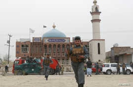 Afghan policemen patrol in front of the Baqir ul Olum mosque on Nov. 21, 2016. Dozens were killed and injured after a suicide bomb attack.