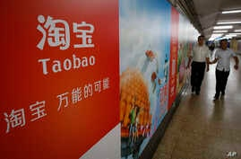FILE - People walk past an advertising billboard showing the mobile app of Alibaba's Taobao consumer-to-consumer site at a subway station in Beijing.