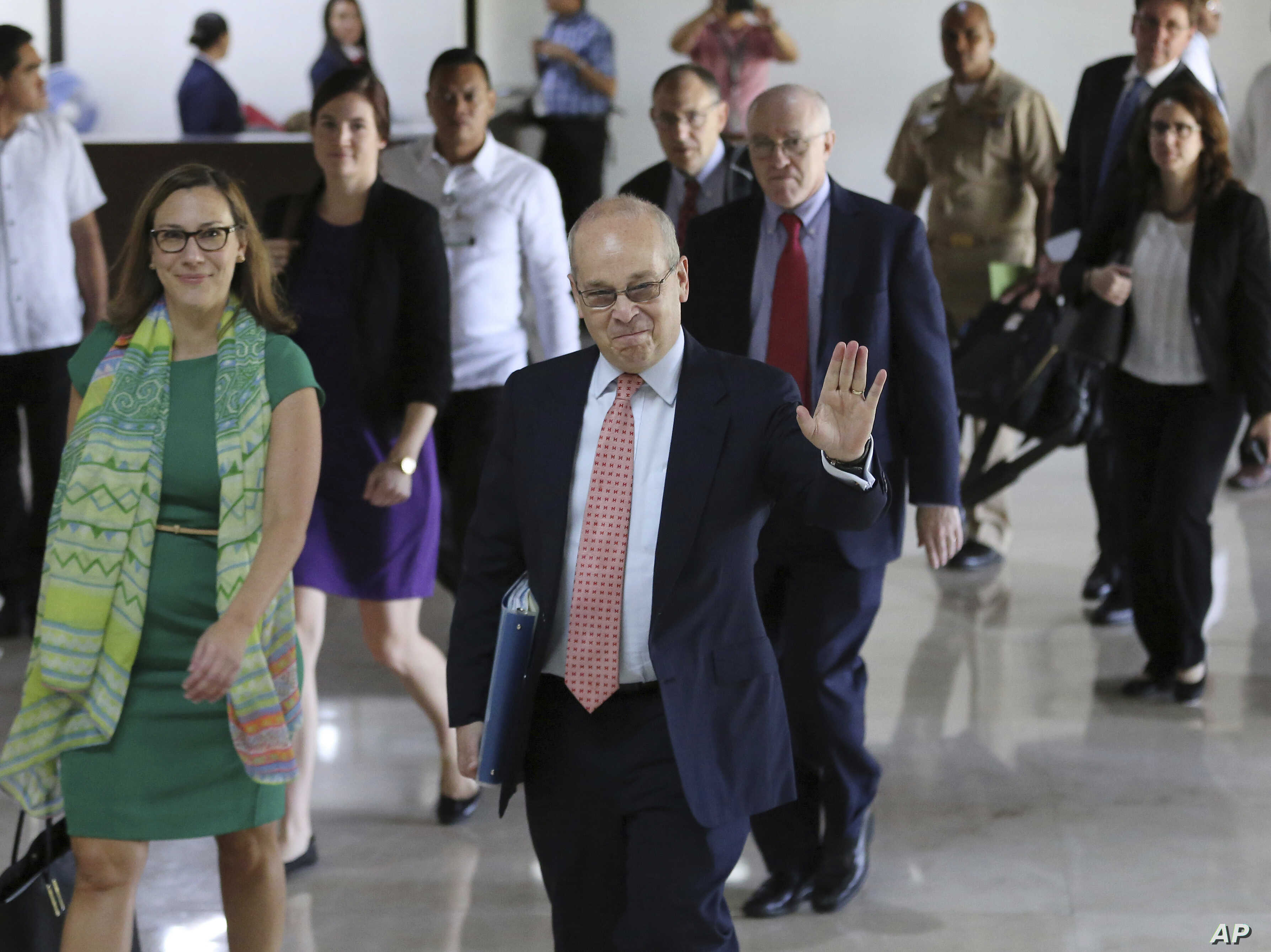 U.S. Assistant Secretary of State for East Asian and Pacific Affairs Daniel Russel, center, waves to reporters before meeting with officials at the Department of Foreign Affairs in suburban Pasay, south of Manila, Philippines, Oct. 24, 2016.