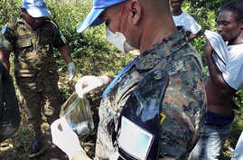 UN peacekeepers from Guatemala take a sample of excrement next to the Nepali UN base in Mirebalais, 27 Oct 2010. UN investigators took samples of foul-smelling waste flowing persistent accusations that excrement from a  Nepalese peacekeeping base cau