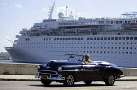 A man drives his convertible car beside the Maltese-flagged 'Thomson Dream' cruiser docked at Havana's port, Dec. 6, 2013.