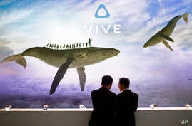Visitor check devices in the Vive HTC booth during the Mobile World Congress in Barcelona, Spain, March 2, 2017.