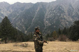 FILE - An Afghan security force personnel keeps watch near his check post in Parun, capital of Nuristan province, Afghanistan.