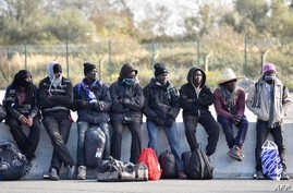 """FILE - Young migrants wait to board a bus leaving for a reception centre, in Calais, on Oct. 28, 2016, following a massive operation to clear the """"Jungle"""" migrant camp."""