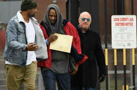 Singer R. Kelly, center, walks with his attorney, Steve Greenberg, right, and an unidentified man, left, who gave him a ride after being released from Cook County Jail, March 9, 2019, in Chicago. Kelly was freed three days after a judge ordered him j