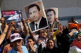 Supporters of former Egyptian President Hosni Mubarak hold his posters and a poster of Egyptian Army Chief Lt. Gen. Abdel-Fattah el-Sissi, left, in front of Tora prison in Cairo, Aug. 22, 2013.