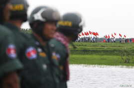 Cambodian police officers stand guard as Vietnamese people wave their national flags across them at the Cambodia-Vietnam border during a visit led by the Opposition Cambodia National Rescue Party (CNRP), in Svay Rieng province July 19, 2015. Lawmaker