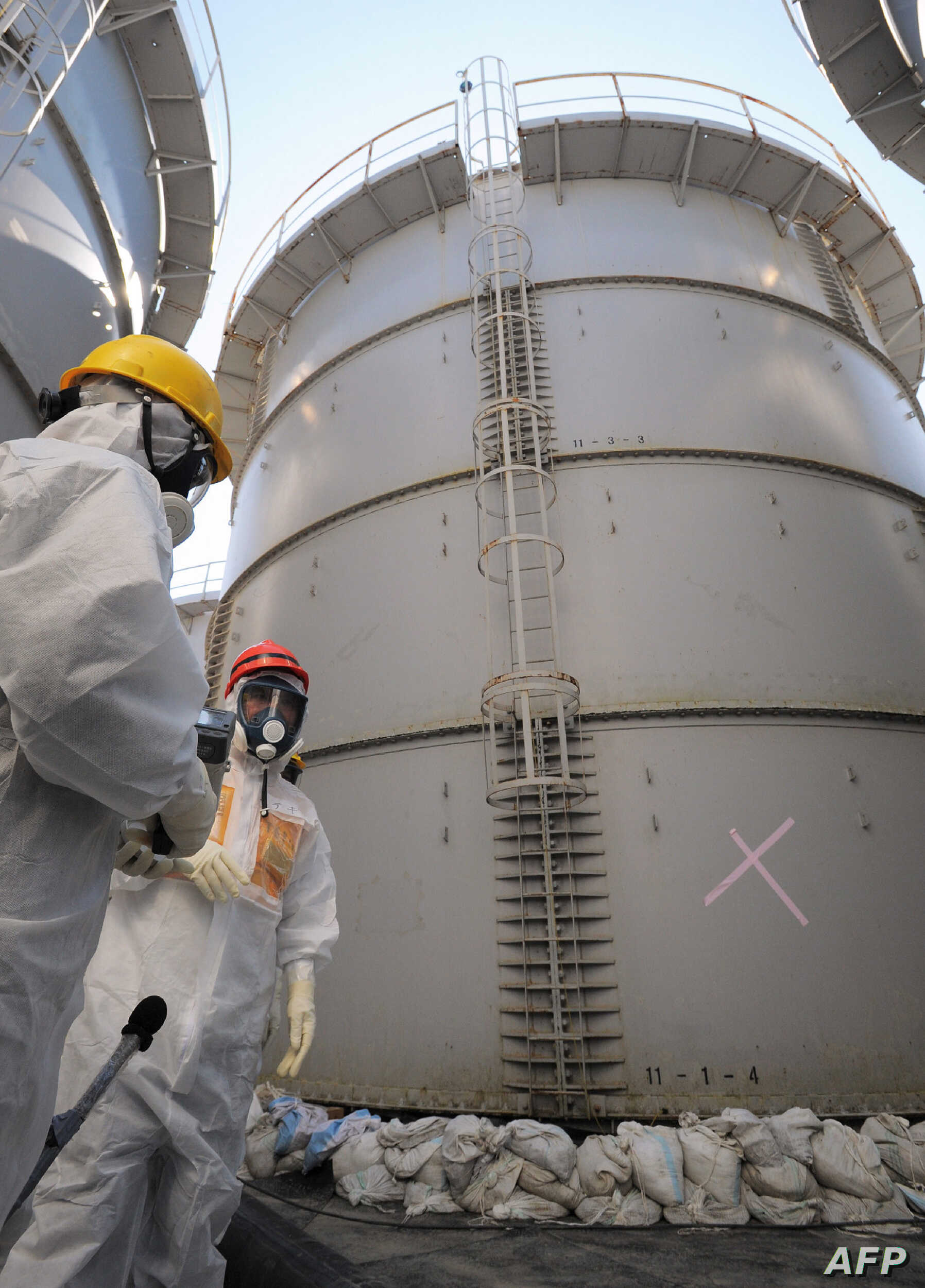 Japanese Economy, Trade and Industry Minister Toshimitsu Motegi (R) in a radiation protection suit inspects a contaminated water tank, found to be have a huge leak of radioactive water, at the Tokyo Electric Power Co (TEPCO) Fukushima Daiichi nuclear