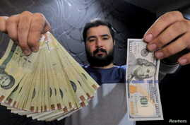 A money changer with a U.S dollar and the amount being given when converting it into Iranian rials at a currency exchange shop in Tehran's business district, January 20, 2016.