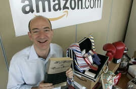 "FILE - Amazon.com founder and CEO Jeff Bezos holds a copy of ""Fluid Concepts and Creative Analogies"" by Douglas Hofstadter - the first book sold online by Amazon.com - as he poses for photos at the company's headquarters in Seattle, Washington, June"