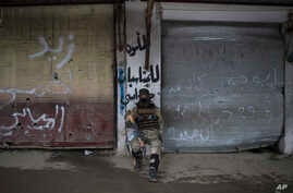 A Iraqi soldier sits in a neighborhood recently retaken by Iraqi security forces during fights with Islamic State militants on the western side of Mosul, Iraq, March 23, 2017.