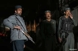Police officers keep watch at the site of an incident in Kabul, November 27, 2014.
