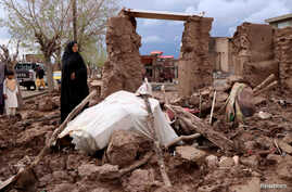 A woman stands next to her house destroyed by flood in Enjil district of Herat province, Afghanistan, March 29, 2019.