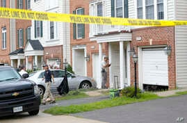 Law enforcement officers are seen outside the home of Nicholas Young, a Washington Metro Transit Officer, Aug. 3, 2016, in Fairfax, Virginia.