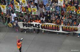 Activists hold a banner as they lead a march of tens of thousands down 6th Avenue during the People's Climate March through Midtown, New York, Sept. 21, 2014.