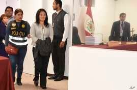 Keiko Fujimori enters the chief prosecutor's office, with a jacket covering her handcuffs, in Lima, Peru, Oct. 10, 2018, in this photo provide by Peru's Justice Department.