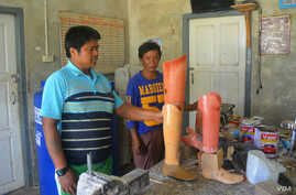 Kyaw Win and his colleague, both former Karenni fighters who lost legs to landmines, look at prosthetic legs in their workshop in Loikaw. (P. Vrieze/VOA)
