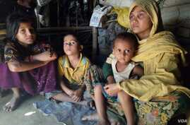 "Habiba, 32, and her three children at a Rohingya village in Bangladesh. According to the Rohingya woman, she was raped by a Burmese soldiers and a Mogh, after her husband was beaten up and taken away from her village in Rakhine in December. ""They loo..."