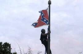 Bree Newsome of Charlotte, N.C., climbs a flagpole to remove the Confederate battle flag at a Confederate monument in front of the Statehouse in Columbia, S.C., June, 27, 2015.