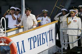 Russian Navy and a Philippine officer salute as Philippine President Rodrigo Duterte alights from the Russian anti-submarine Navy vessel Admiral Tributs in Manila, Philippines, Jan. 6, 2017.