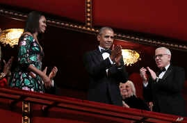 President Barack Obama and first lady Michelle Obama, with financier and philanthropist David Rubenstein, right, applaud during the Kennedy Center Honors Gala at the Kennedy Center in Washington, Dec. 4, 2016.