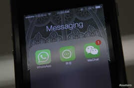 FILE - Icons of messaging applications WhatsApp of Facebook (L), Laiwang of Alibaba Group (C) and WeChat, or Weixin, of Tencent Group, are seen on the screen of a smart phone on this photo illustration taken in Beijing, February 24, 2014.